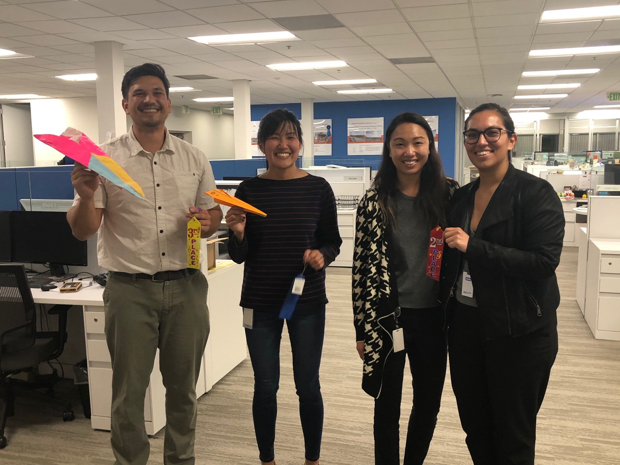 Harris employees celebrating National Engineers Week with a paper airplane competition.